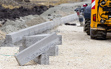 Kerb stones on gravel ground for placing road edge at construction site